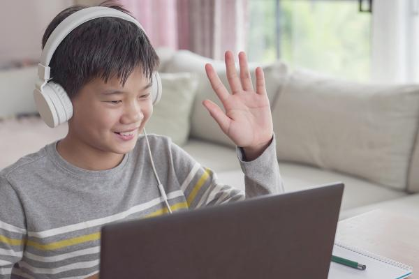 A teenager is seated in his living room with a laptop and headphones. He smiles and waves at the computer screen. - Un adolescent est assis dans son salon avec un ordinateur portable et des écouteurs. Devant son écran d'ordinateur, il sourit et salue de la main.