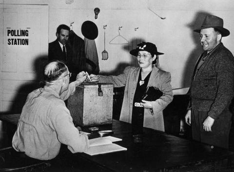 Photograph of a Japanese woman casting her ballot in a polling station.