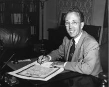 Photographie en noir et blanc de Tommy Douglas assis à son bureau, signant un document officiel et souriant à la caméra.